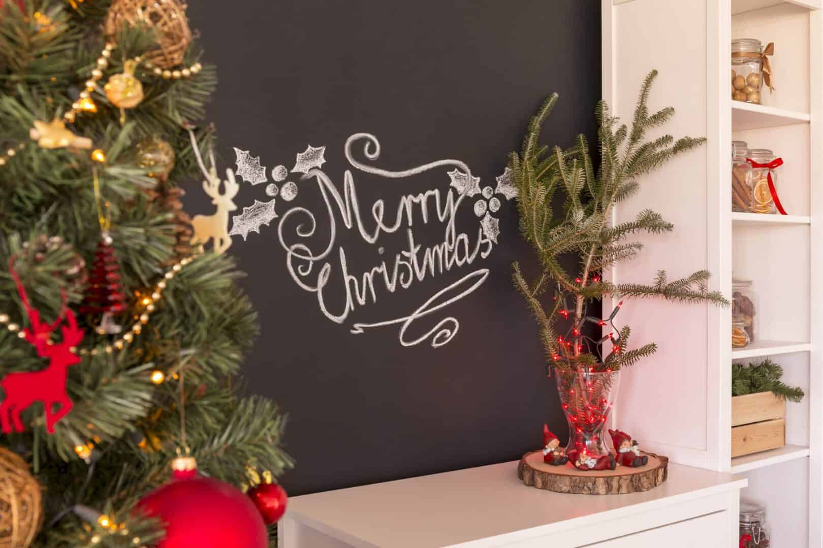 Merry christmas sign n a blackboard above commode with decorations