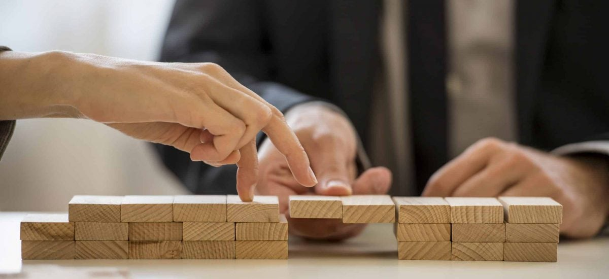 Business teamwork and cooperation concept - male hand supporting a bridge made of wooden pegs for a female hand to walk its fingers across towards promotion and progress.