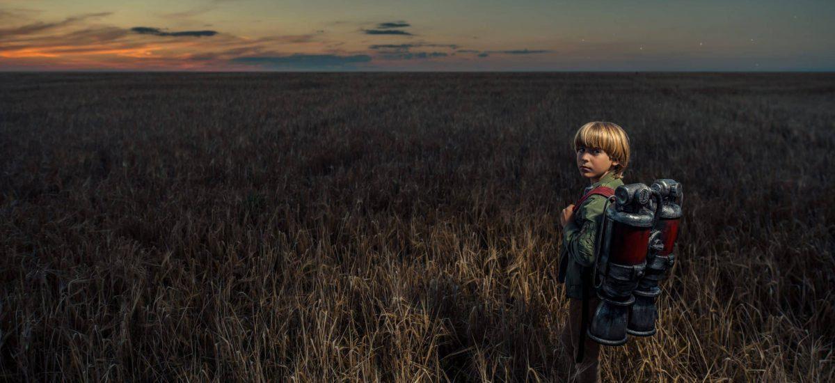Little boy wit a backpack in a field