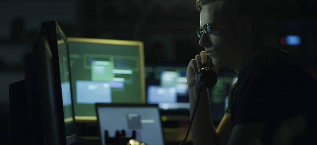 Hacker with sunglasses holding a telephone receiver and computer screens, coding and system hacking concept