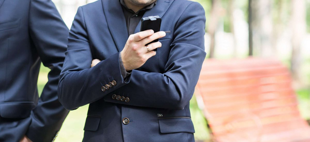 Young urban professional man using smart phone. Businessman holding mobile smartphone using app texting sms message.